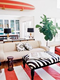 Red rules in this elegant coastal room with Surfboard Decor. Black is a popular choice to contrast red, and I have seen black and white animal prints mixed with coastal before. Bold Living Room, Coastal Living Rooms, Home And Living, Living Spaces, Living Area, Modern Living, Surfboard Decor, Surf Decor, Arquitetura