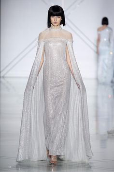 White and silver foil basket-weave organza gown and cape with sheer tulle pleated neckline, hand encrusted with glass beads and pearls.