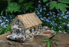 This is a hand crafted illuminated Stone Cottage. Can be used as a Fairy House, in an outdoor garden display or by itself as a center piece. The house is crafted using solid pine wood and real stones. Doors are hinged and operational while the interior is unfinished . The light for illumination is a battery powered Tea type light. The overall size is approximately 6w x 8l x 6h.  Included in this sale is the Stone Cottage pictured and the light.