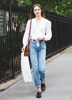 Model Tilda Lindstam in a simple white button-down, loose jeans and loafers