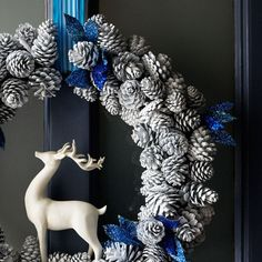 I like the pine cones but the deer needs to be wood or antiqued brass and the blue needs replaced with green pine or holly sprays with red berries and maybe natural fiber ribbon.