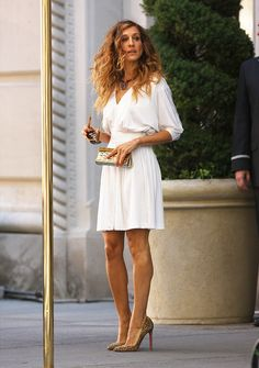Sarah Jessica Parker (aka Carrie Bradshaw) wears a white sleeved dress and leopard pumps.
