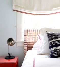 Black-and-white striped sham in bedroom with modern table lamp