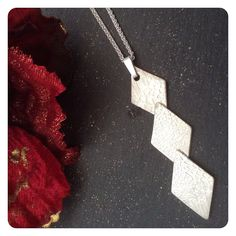 Handmade sterling silver diamond shaped pendant.  A trio of shapes have been embossed and made into this contemporary shaped pendant.  Something a bit different.  Measures approx 5cm from top of bail. Comes on an 18 inch sterling silver chain.  Presented in a White jewellery box.