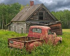 Rusty red truck beside run down old house.