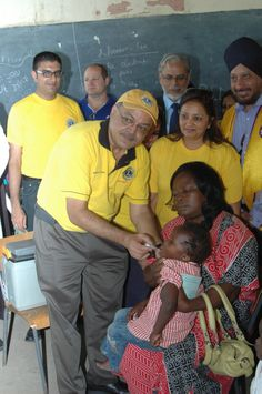 PID Dr. Manoj Shah vaccinates a child with oral Polio drops at the Mukuru Centre where Lions celebrated WIW 2014.