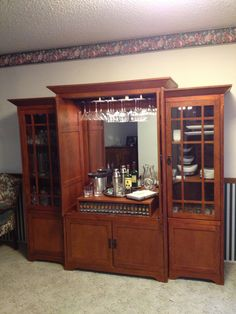 Repurposed entertainment center. I added a bathroom mirror, closet light, and stemware holders to make this a bar!