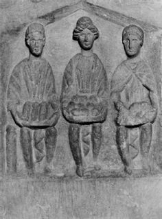 Three Mother Goddesses on a stone from Cirencester. They holdloaves, apples and ears of corn. Courtesy Corinium Museum, Cirencester. Ht78 cm. ©Cotswold District Council.