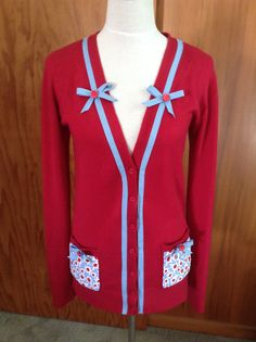 Cardigan embellished with vintage fabric pockets, bias binding bows and trim, and retro buttons.