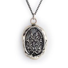 This handcrafted talisman necklace reads Toujours le Meme in French, which means Always the Same. The jasmine branches represent devotion and constancy. Each Pyrrha talisman is cast in reclaimed sterling silver or bronze from a 19th century wax seal and is handcrafted in Vancouver, Canada. Approx. 5/8 x 7/8.