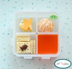 Here's a fishy little bento box. She got some fish shaped marble cheese with a food safe marker eye, some crackers with a little chocolate goldfish, a container of orange jello and a peeled clementine orange with an adorable little leaf pick. All of the picks in this week's bento boxes can be found at All Things for Sale (link in sidebar).