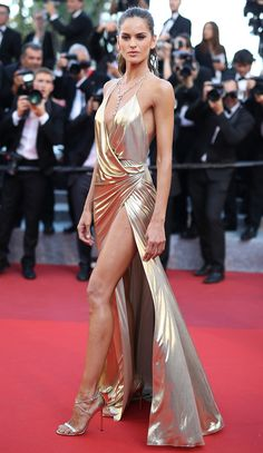 IZABEL GOULART goes for a '70s-inspired gold lamé gown with a high slit and faux-rap, plus a pendant necklace and metallic heels, for the Last Face premiere.