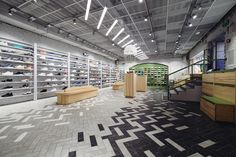 Fusing old and new, the setting incorporates the original brick walls, albeit dipped in a white hue, and paired with a gradient white to black tiled flooring, and a ceiling superimposed by a industrial-looking metal grid. Visual Merchandising, Dropped Ceiling, Sneaker Stores, Retail Interior, Floor Patterns, Branding, Retail Space, Shop Interiors, Design Furniture