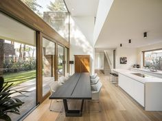 This modern house has a double-height ceiling above dining table large windows for plenty of natural light and wood framed sliding doors to connect to the outdoors. Dining Room Table Decor, Dining Room Design, Kitchen Dining, Dining Tables, Küchen Design, Interior Design, Design Trends, Design Ideas, Traditional Dining Rooms