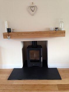 Wood burning stove, oak beam, slate hearth, modern Scandinavian