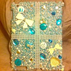 Tiffany's themed iPad 2 case This case was handmade by myself. For all of you Tiffany's lovers this is perfect for your iPad 2! I used Tiffany's themed charms and pins, cabochons, high quality crystals, metal and plastic bows, white and blue pearls, and gems. This case took me 2 long weeks to complete. The case also comes with a bag of extra stones and pearls. Tiffany & Co. Accessories Tablet Cases