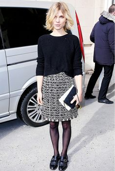 Clemence Poésy wears a black sweater, tweed mini skirt, tights, and oxfords