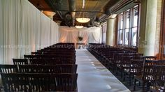 "Elegant Event Lighting Chicago designed a beautiful ""L"" shaped, pleated ivory fabric drape wall that was illuminated with warm amber uplighting. The decorative drape design created the perfect backdrop for the couple to exchange vows."