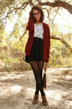 violet cardigan with a floral t -shirt, paired with a black high wasted skirt black stalkings,  and tan ankle high boots.