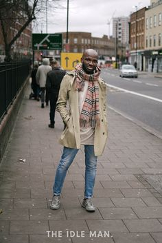 Men's street style, a camel coat with a thick scarf and a white long sleeved tee, light blue skinnies and a pair of Converse Chuck Taylors | The Idle Man