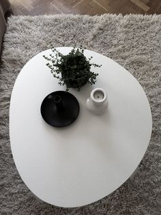 Living space: modern white round coffee table/grey rug/parquet floor