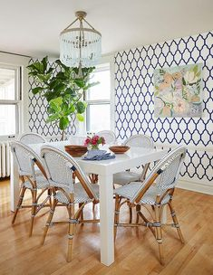 Lovely dining space features a turquoise beaded chandelier, Ro Sham Beaux Malibu Chandelier, illuminating a white West Elm Parsons Dining Table lined with navy French bistro chairs, Serena & Lily Riviera Side Chairs, surrounded by walls clad in navy trellis wallpaper lined with a low chair rail.