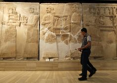 A man walks past a Babylonian period artifact inside the National Museum of Iraq in Baghdad.