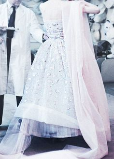 Vintage View: detail of a classic pale pink embroidered gown with layers of luxurious draped fabric being adjusted in the atelier of Christian Dior, 1957.