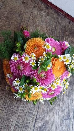 Pretty pink and orange dahlias with matricaria daisies and hypericum berries with pink organza ribbon finish
