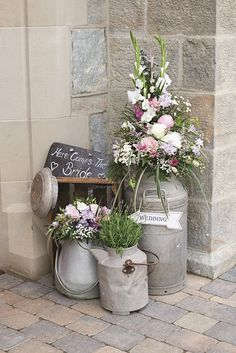 A vignette featuring an assortment of vintage milk churns and flowers. Picture…