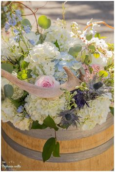 Large, wine barrel piece.  Hydrangea, roses, thistle, and wax flower. Pink Blue and White Flowers and antlers.