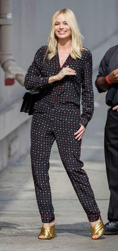 Margot Robbie in pajama-esque Thakoon pants and top and gold Gucci heels