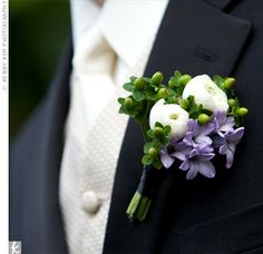 boutonniere, composed of green hypericum berries, white ranunculus, and purple lilac blossoms...the knot