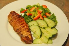 Marinated chicken in balsamic vinegar, garlic, salt, pepper, and a little olive oil.  With a small salad with a sliced strawberry over the top and some slices of cucumbers on the side.