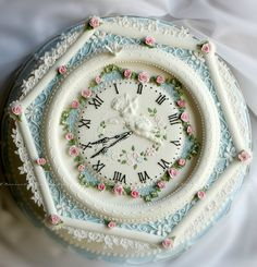 Exquisite clock cake with royal icing scroll and flower work. Just unbelievable. This person is a genius.