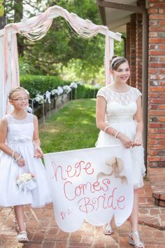"""Flower girls carry """"here comes the bride"""" sign painted on canvas with burlap"""