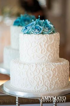 A two-tiered white-and-gold wedding cake with a gold striped accent, from…