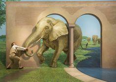 """Una visitante simula tirar de la trompa de un elefante en la galería """"El parque natural del faraón"""" dentro del museo de Arte Takao Trick en Hachioji, al oeste de Tokio, Japón."""