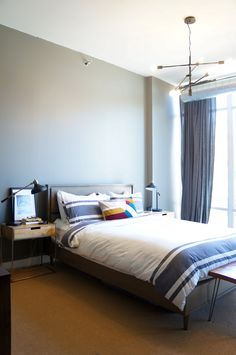 This Chelsea Grey wall paint in the bedroom is an amazing blue-ish grey color. The wood nightstands and bench at the foot of the bed pop right out.