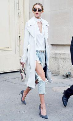 Gigi Hadid wears a turtleneck cutout top, long coat, boyfriend jeans, pumps, a cool clutch, and round sunglasses