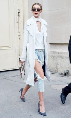 Gigi Hadid wears a turtleneck cutout top, long coat, boyfriend jeans, pumps, a cool clutch, and round sunglasses