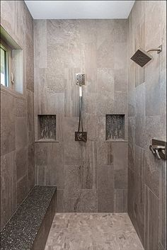 Walkin-in shower with dual shower heads, niches, and a bench with Cambria quartz.