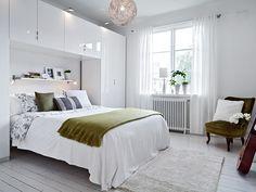 pont de lit blanc, moderne et fonctionnel et une étagère murale blanche dans la chambre à coucher blanche aux accents vert olive