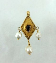 Byzantine gold pendant with pearls Ca 700 A.D. gold pendant with tear drop cabochon garnet in the middle.Original attached loop on top.3 natural pearls . The pearls are exceptional quality. Measurements : 39 mm including the hanging pearl. Without the pearl but including the loop 24 mm