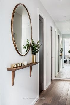 Chic foyer hallway features a round gold oversized mirror placed over a walnut s…  http://www.nicehomedecor.site/2017/08/07/chic-foyer-hallway-features-a-round-gold-oversized-mirror-placed-over-a-walnut-s/