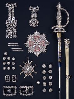 The sword, scabbard and decorations are self-explanatory, but look at the bottom left of this picture: these are shoe buckles. Above are the smaller buckles that tied the breeches just under the knee. And note the set of diamond buttons, smaller (left) for the waistcoat and larger (center right) for the coat.