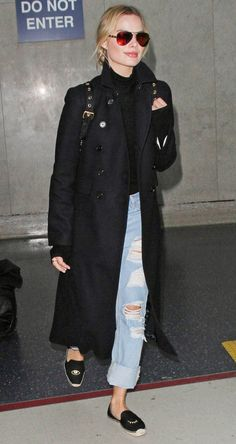 Margot Robbie in ripped jeans, a black trench coat, turtleneck and Soludos espadrilles