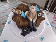 Brief for this cake: old man on brown leather sofa, bald, grey on sides with glasses, reading a newspaper, black shggy dog, and brown and white cat! Think i managed it!