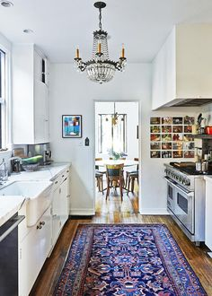 A chandelier and tribal rug transform a plain and simple kitchen into a more luxurious space. Food is the unifying theme in the collection of photographs on the wall.