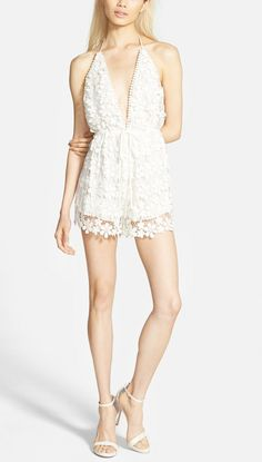 Adoring the lacy floral embroidery that covers this halter-style romper featuring a plunging front neckline and an open back.